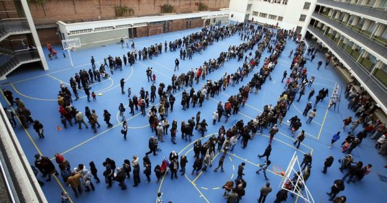 People queue at a polling station to cast their ballots in a symbolic independence vote in Barcelona